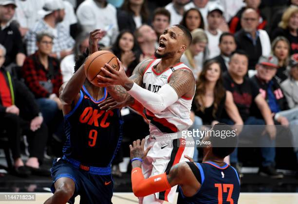 Damian Lillard of the Portland Trail Blazers drives to the basket on Jerami Grant and Paul George of the Oklahoma City Thunder during the second half...