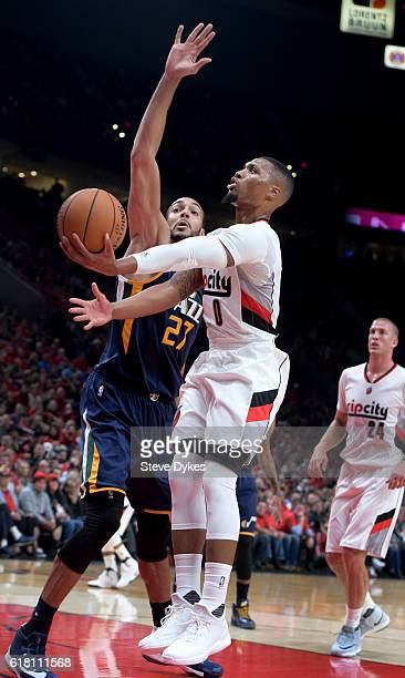 Damian Lillard of the Portland Trail Blazers drives to the basket on Rudy Gobert of the Utah Jazz in the first quarter of an NBA game at the Moda...