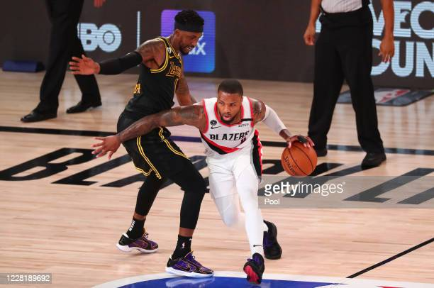 Damian Lillard of the Portland Trail Blazers drives to the basket against Kentavious CaldwellPope of the Los Angeles Lakers in the first half in game...