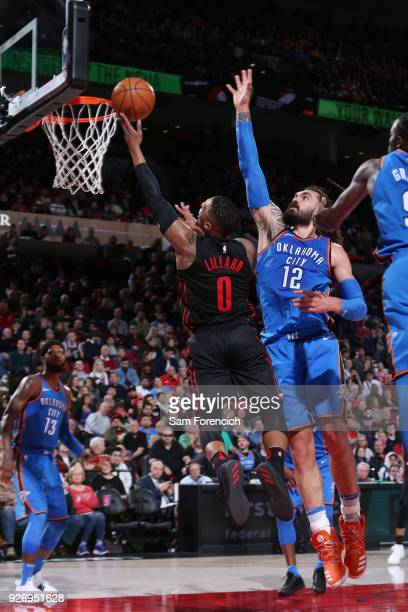 Damian Lillard of the Portland Trail Blazers dunks against Steven Adams of the Oklahoma City Thunder on March 3 2018 at the Moda Center in Portland...