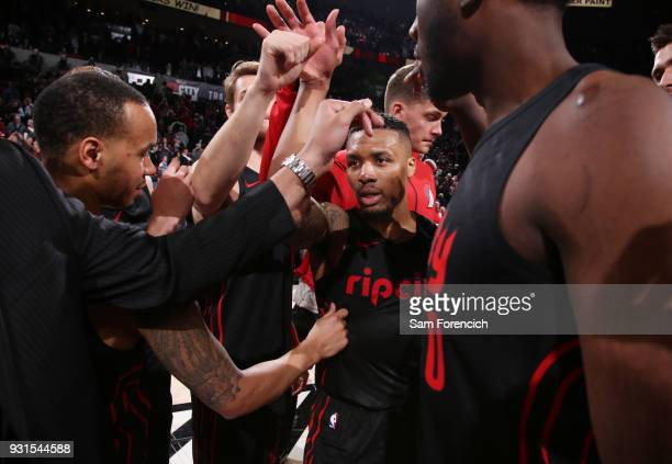 Damian Lillard of the Portland Trail Blazers exchanges high fives with teammates during the game against the Golden State Warriors on March 9 2018 at...