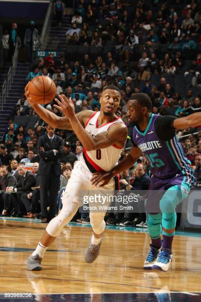 Damian Lillard of the Portland Trail Blazers handles the ball against Kemba Walker of the Charlotte Hornets on December 16 2017 at Spectrum Center in...