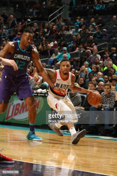 Damian Lillard of the Portland Trail Blazers handles the ball against Dwight Howard of the Charlotte Hornets on December 16 2017 at Spectrum Center...