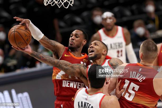 Damian Lillard of the Portland Trail Blazers is blocked going to the basket by Monte Morris of the Denver Nuggets in the fourth quarter during Game...