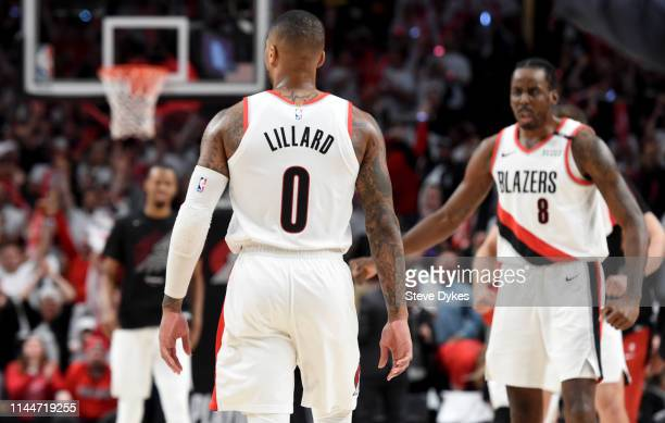 Damian Lillard of the Portland Trail Blazers is greeted by AlFarouq Aminu as he comes to the bench after hitting a shot during the second half of...