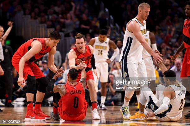 Damian Lillard of the Portland Trail Blazers is helped up by teammates Pat Connaughton and Zach Collins as Jamal Murray of the Denver Nuggets is...
