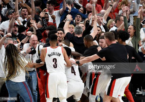 Damian Lillard of the Portland Trail Blazers is mobbed by teammates after hitting the game winning shot in Game Five of the Western Conference...