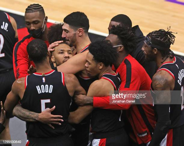 Damian Lillard of the Portland Trail Blazers is mobbed by teammates after hitting the game-winning three point shot against the Chicago Bulls at the...