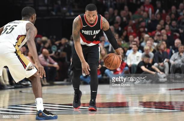 Damian Lillard of the Portland Trail Blazers looks to get past E'Twaun Moore of the New Orleans Pelicans drives to the basket during the fourth...