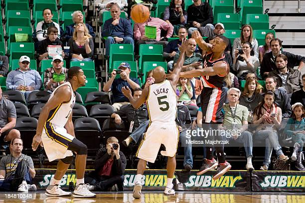 Damian Lillard of the Portland Trail Blazers passes against Derrick Favors and John Lucas III of the Utah Jazz at Energy Solutions Arena on October...