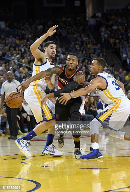 Damian Lillard of the Portland Trail Blazers passes the ball while guarded by Klay Thompson and Stephen Curry of the Golden State Warriors during an...