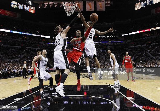 Damian Lillard of the Portland Trail Blazers shoots between Tiago Splitter and Kawhi Leonard of the San Antonio Spurs in Game Five of the Western...