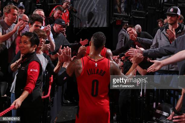 Damian Lillard of the Portland Trail Blazers walks off the court and shakes hands with fans after the game against the Cleveland Cavaliers on March...