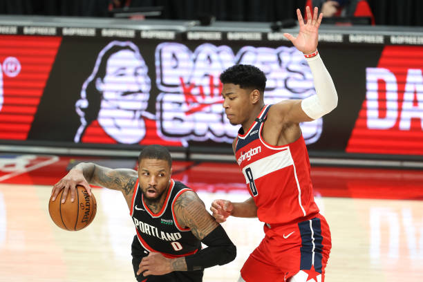 Damian Lillard of the Portland Trail Blazers works against Rui Hachimura of the Washington Wizards in the fourth quarter at Moda Center on February...