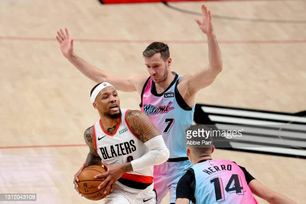Damian Lillard of the Portland Trail Blazers works towards the basket against Goran Dragic and Tyler Herro of the Miami Heat in the third quarter at...