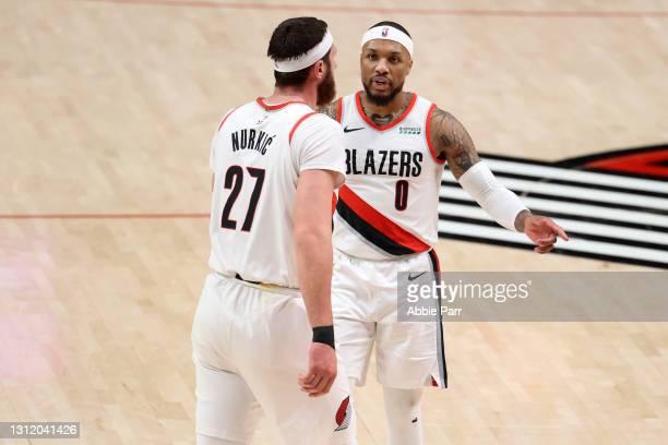 Damian Lillard reacts alongside Jusuf Nurkic of the Portland Trail Blazers in the third quarter against the Miami Heat at Moda Center on April 11,...