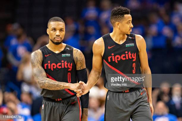 Damian Lillard shakes hands with CJ McCollum of the Portland Trail Blazers during a game against the Oklahoma City Thunder during Round One Game...
