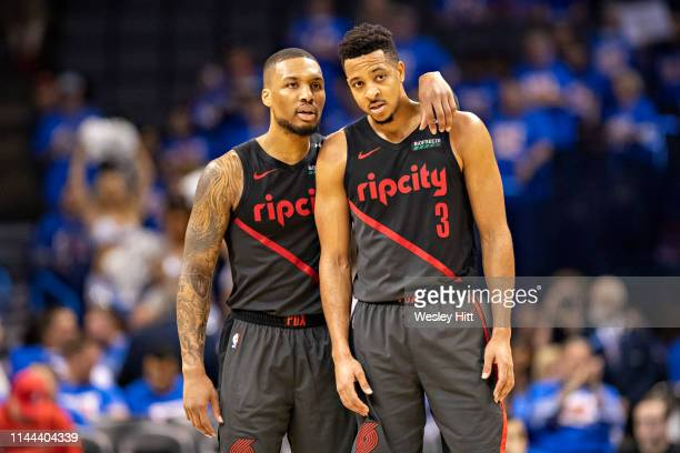 Damian Lillard talks with CJ McCollum of the Portland Trail Blazers during a game against the Oklahoma City Thunder during Round One Game Three of...