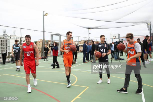 Damian Martin of the Perth Wildcats and Alexander Loughton of the Cairns Taipans shoot baskets with AFL players Josh Kelly and Toby Greene of the GWS...