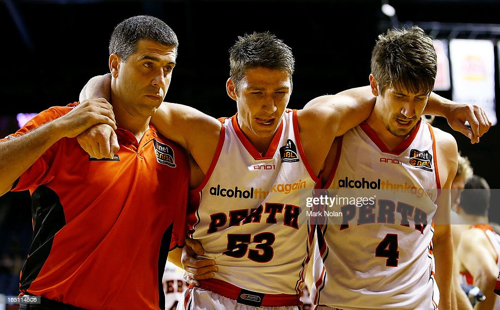 Damian Martin of the Wildcats is assisted from the court with an ankle injury during game two of the NBL Semi Final series between the Wollongong Hawks and the Perth Wildcats at WIN Entertainment Centre on March 31, 2013 in Wollongong, Australia.