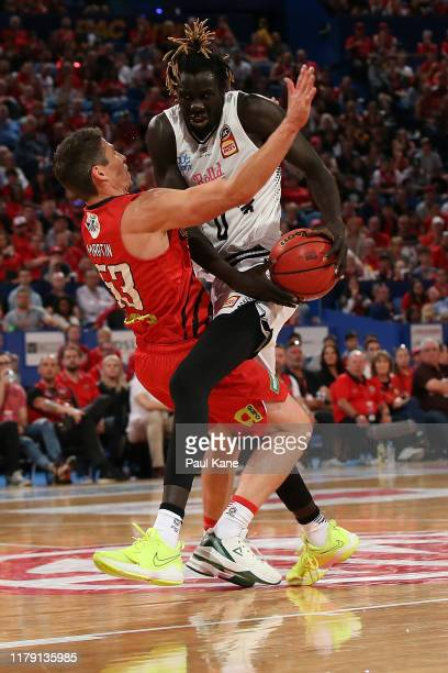 Damian Martin of the Wildcats is charged by Jo LualAcuil of United during the round one NBL match between the Perth Wildcats and Melbourne United at...