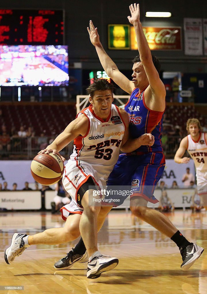 Damian Martin of the Wildcats tries to dribble past Jason Cadee of the 36ers during the round six NBL match between the Adelaide 36ers and the Perth Wildcats at Adelaide Arena on November 11, 2012 in Adelaide, Australia.