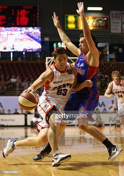 Damian Martin of the Wildcats tries to dribble past Jason Cadee of the 36ers during the round six NBL match between the Adelaide 36ers and the Perth...