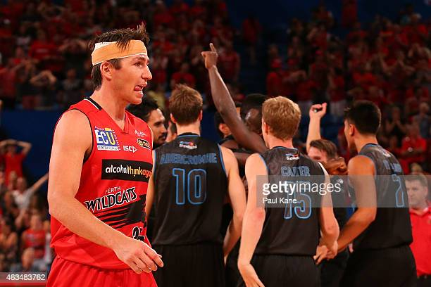 Damian Martin of the Wildcats walks from the court as the Breakers celebrate after a three point shot by Cedric Jackson to win the game in double...