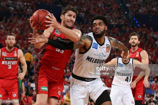 Damian Martin of the Wildcats wins a loose ball possession against DJ Kennedy of United during game one of the NBL Grand Final Series between the...