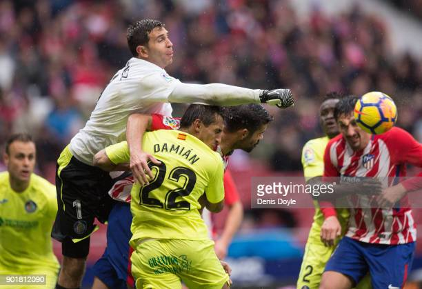 Damian Martinez of Getafe punches the ball away from Diego Costa of Atletico Madrid during the La Liga match between Atletico Madrid and Getafe at...
