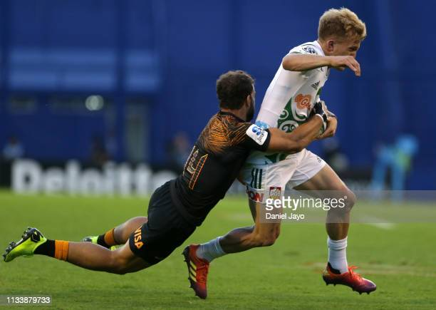 Damian McKenzie of Chiefs is tackled by Ramiro Moyano of Jaguares during a Super Rugby Rd 7 match between Jaguares and Chiefs at Jose Amalfitani...