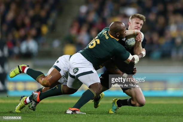 Damian McKenzie of the All Blacks is tackled by Bongi Mbonambi and Elton Jantjies of the Springboks during The Rugby Championship match between the...