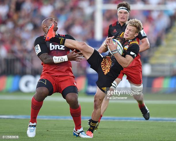 Damian McKenzie of the Chiefs charges over Nemani Nadolo of the Crusaders during the round one Super Rugby match between the Crusaders and the Chiefs...