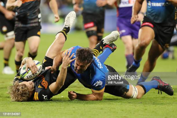 Damian McKenzie of the Chiefs is tackled by Jeremy Thrush of the Force during the round one Super Rugby Trans-Tasman match between the Western Force...