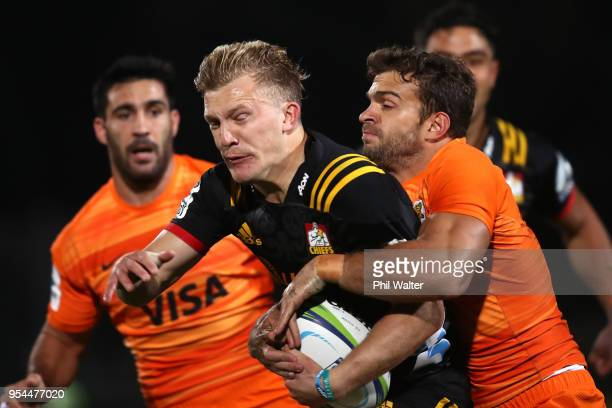 Damian McKenzie of the Chiefs is tackled by Ramiro Moyano of the Jaguares during the round 12 Super Rugby match between the Chiefs and the Jaguares...