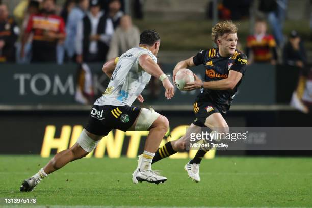 Damian McKenzie of the Chiefs looks to beat the tackle of Devan Flanders of the Hurricanes during the round nine Super Rugby Aotearoa match between...