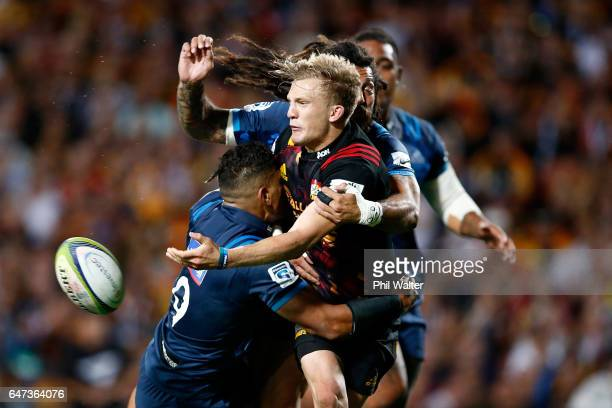 Damian McKenzie of the Chiefs offloads the ball during the round two Super Rugby match between the Chiefs and the Blues at Rugby Park on March 3 2017...