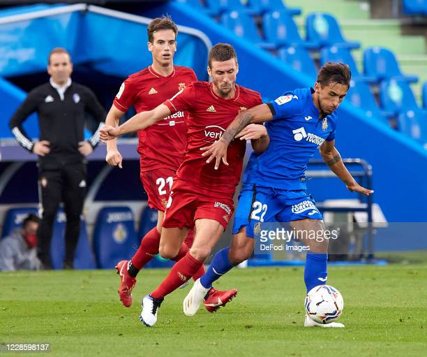 Damian Suarez of Getafe CF and Oier of CA Osasuna battle for the ball during the La Liga Santander match between Getafe CF and CA Osasuna at Coliseum...