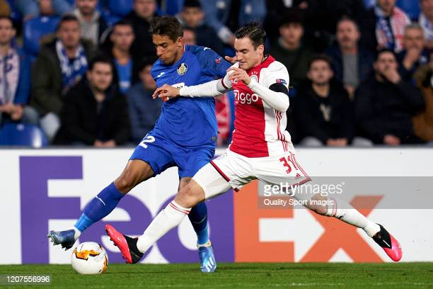 Damian Suarez of Getafe CF battle for the ball with Nicolas Tagliafico of AFC Ajax during the UEFA Europa League round of 32 first leg match between...
