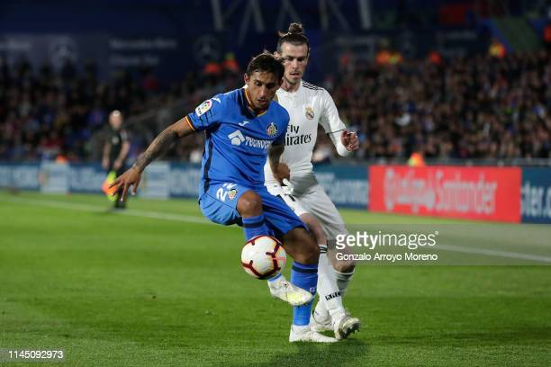 Damian Suarez of Getafe CF competes for the ball with Gareth Bale of Real Madrid CF during the La Liga match between Getafe CF and Real Madrid CF at...
