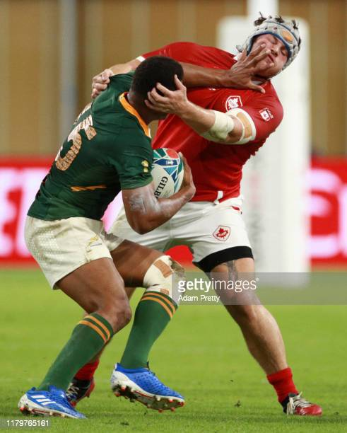 Damian Willemse of South Africa fends off Andrew Quattrin of Canada during the Rugby World Cup 2019 Group B game between South Africa and Canada at...