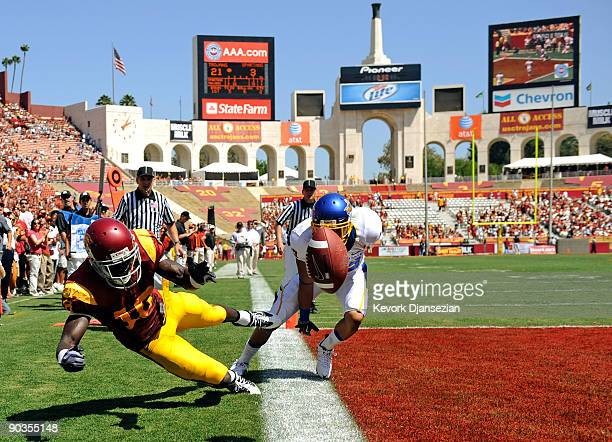 Damian Williams of the USC Trojans drops the ball while falling out of the end zone after Brandon Rutley of the San Jose State Spartans broke up the...