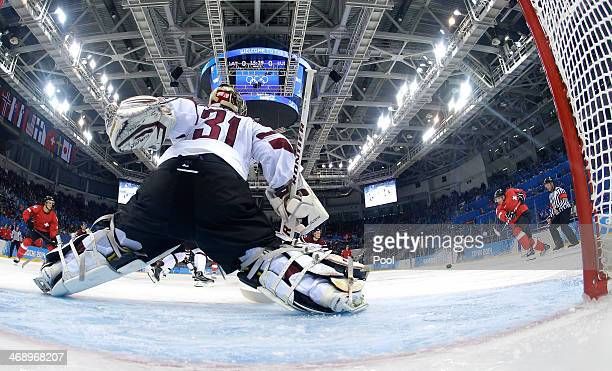 Damien Brunner of Switzerland shoots against Edgars Masalskis of Latvia in the second period during the Men's Ice Hockey Preliminary Round Group C...