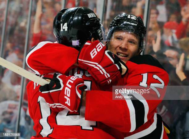 Damien Brunner of the New Jersey Devils celebrates with teammate Adam Henrique after scoring his second goal of the game during the third period...
