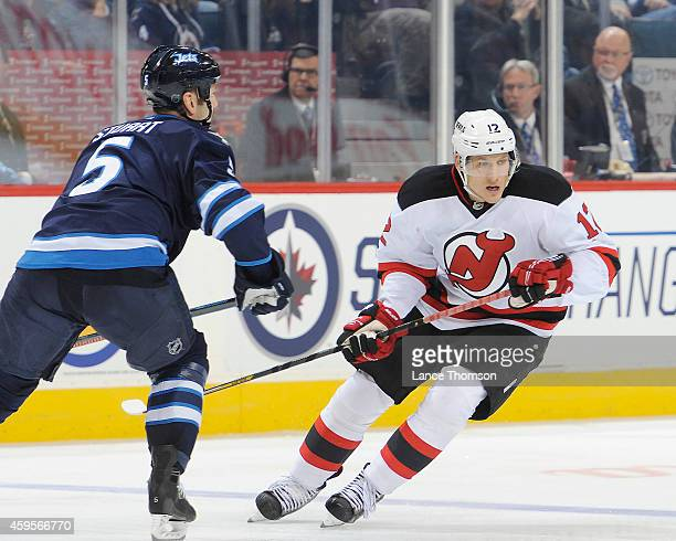 Damien Brunner of the New Jersey Devils follows the play down the ice as Mark Stuart of the Winnipeg Jets defends during third period action on...