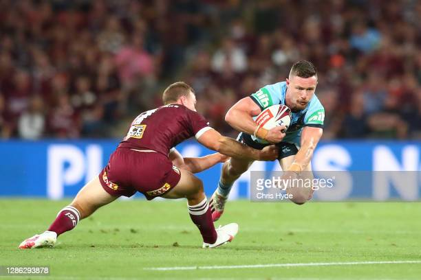 Damien Cook of the Blues is tackled by Daly CherryEvans of the Maroons during game three of the State of Origin series between the Queensland Maroons...