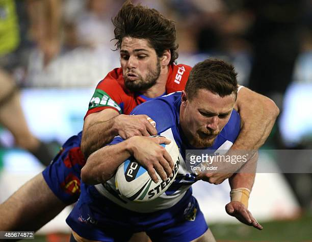 Damien Cook of the Bulldogs is tackled by Jake Mamo of the Knights during the round 25 NRL match between the Newcastle Knights and the Canterbury...