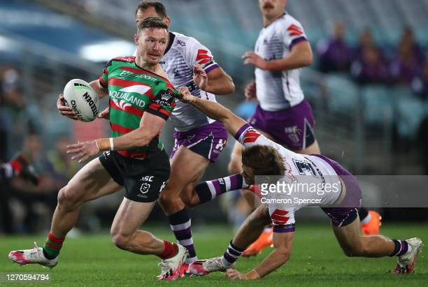 Damien Cook of the Rabbitohs is challenged by Ryan Papenhuyzen of the Storm during the round 17 NRL match between the South Sydney Rabbitohs and the...