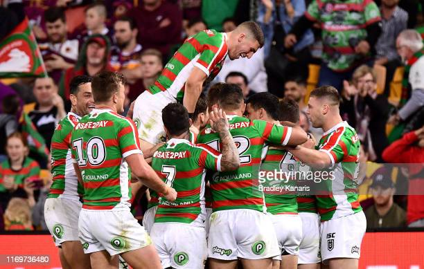 Damien Cook of the Rabbitohs is congratulated by team mates after scoring a try during the round 23 NRL match between the Brisbane Broncos and the...