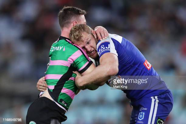 Damien Cook of the Rabbitohs is tackled by Aiden Tolman of the Bulldogs during the round 22 NRL match between the South Sydney Rabbitohs and the...